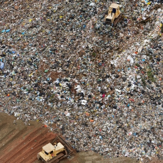 Bulldozer pushing garbage in landfill